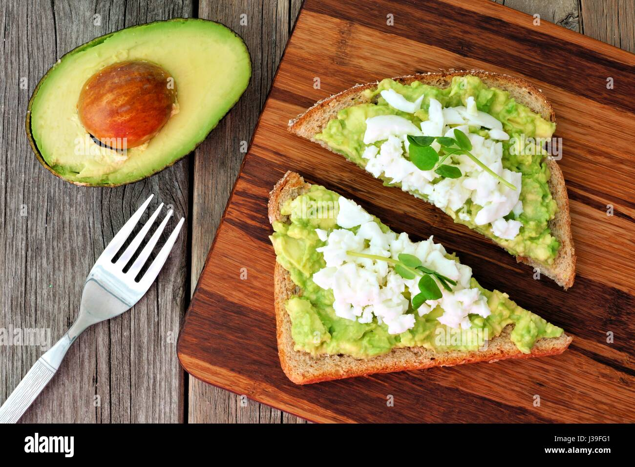 Avocado toast with egg whites and pea shoots on wooden board, overhead view - Stock Image