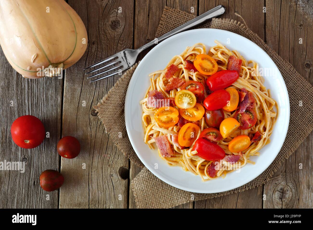 Creamy butternut squash pasta dish with bacon and cherry tomatoes, above view on rustic wood - Stock Image