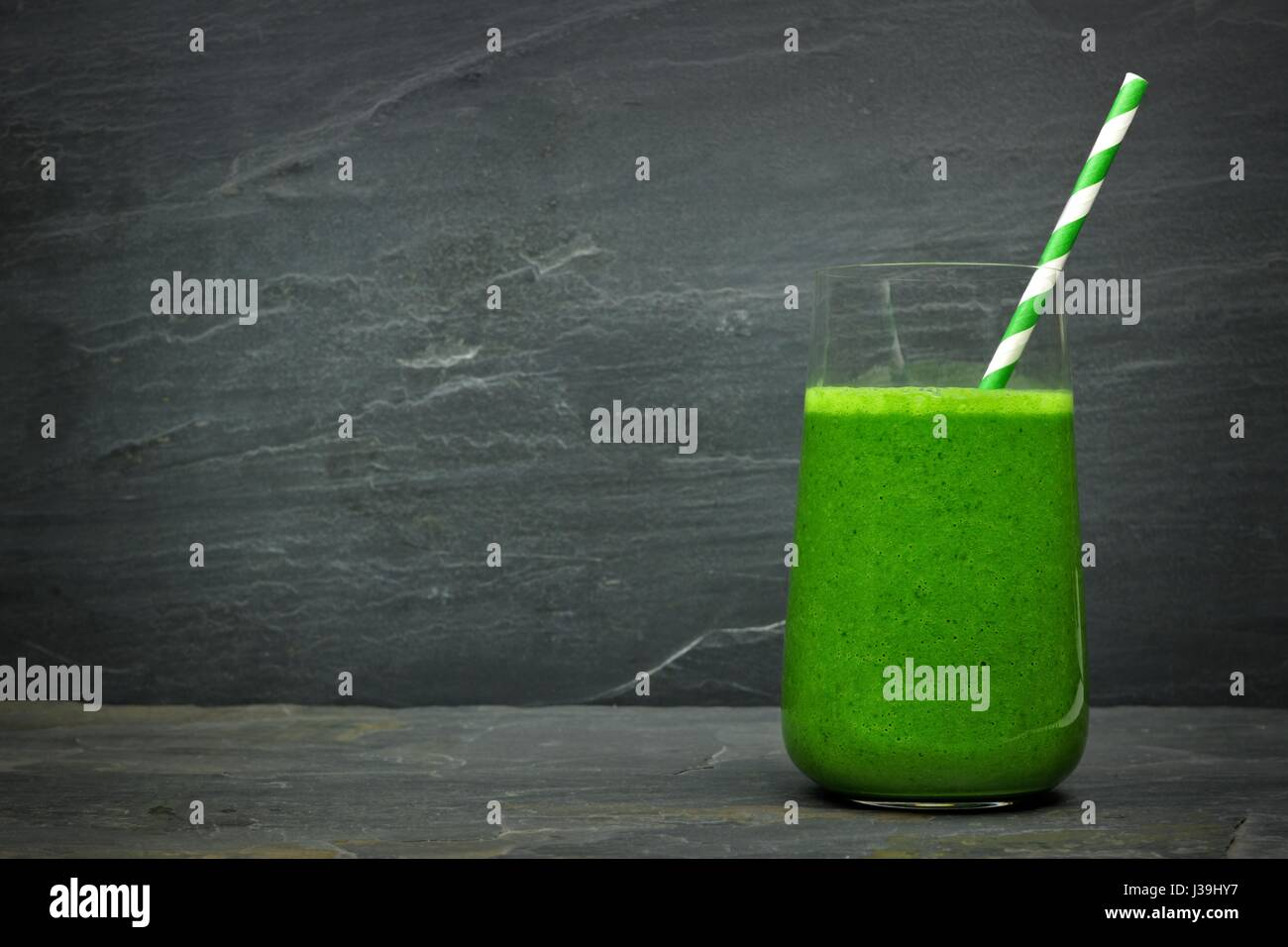 Green kale smoothie in a glass with straw on a dark slate stone background Stock Photo