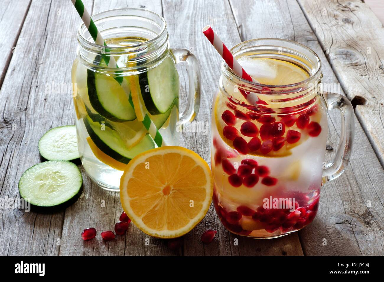 Detox water in mason jar glasses with lemon, cucumber and pomegranate against a rustic wood background - Stock Image