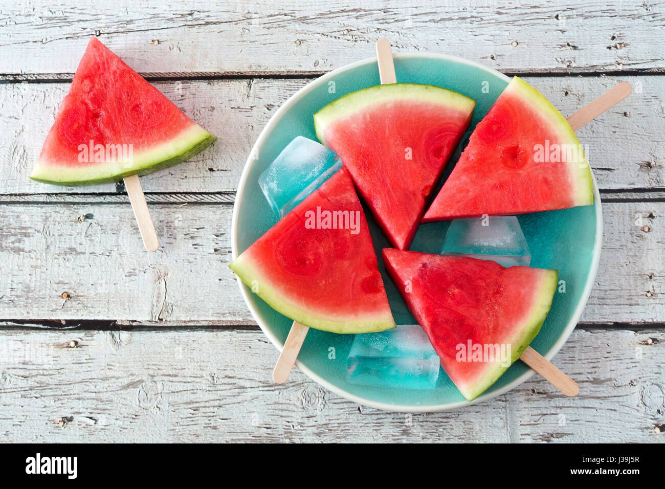 Watermelon slice popsicles on a vintage blue plate and rustic wood background - Stock Image