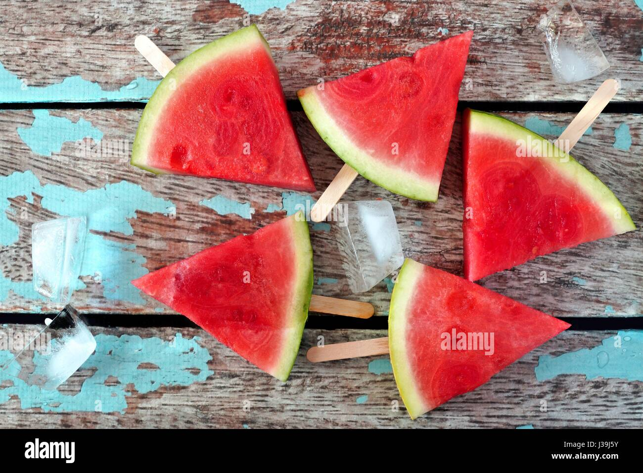 Group of watermelon slice popsicles on a rustic blue wood background - Stock Image
