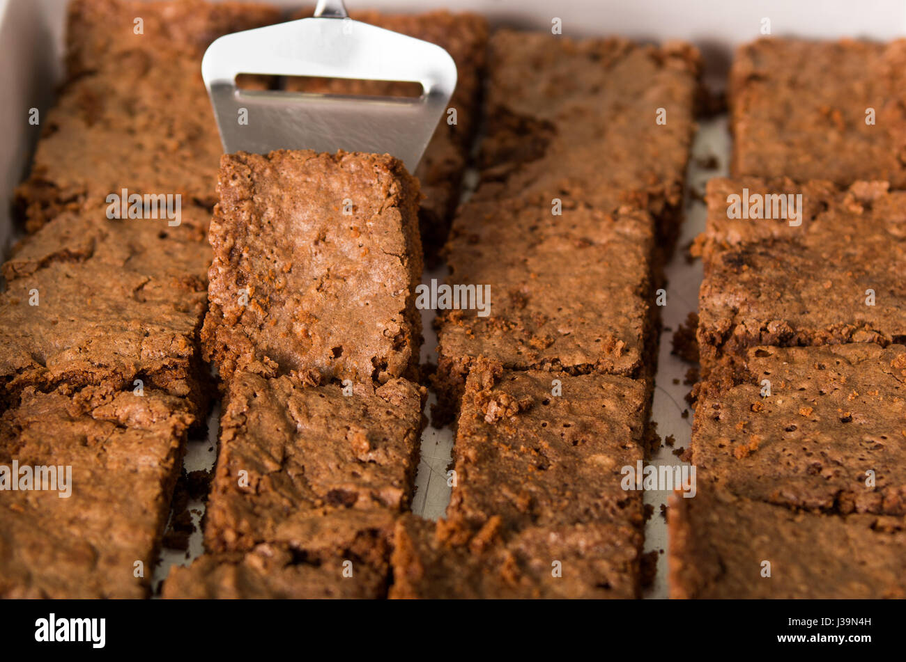 Delicious brown colored chocolate brownies lined up, square pieces as seen from above angle, metal cake cutter being Stock Photo
