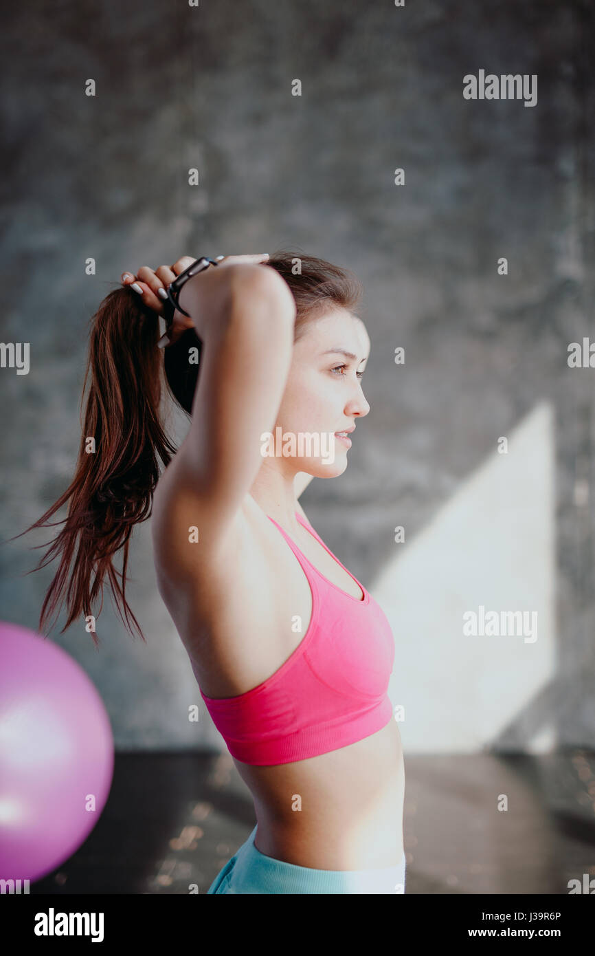 Womans break in workout to tie her hair. Female athlete tying hair before her workout with dumbbells. Beautiful - Stock Image