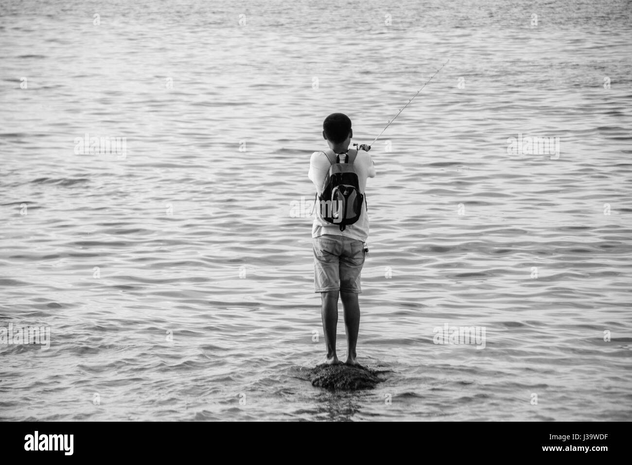 Man casting his fishing rod into the sea, Stock Photo
