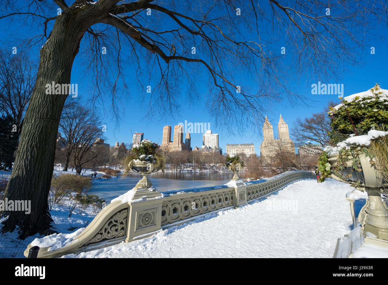 Scenic view from the landmark Bow Bridge of Central Park covered in snow on a bright winter morning after a storm Stock Photo