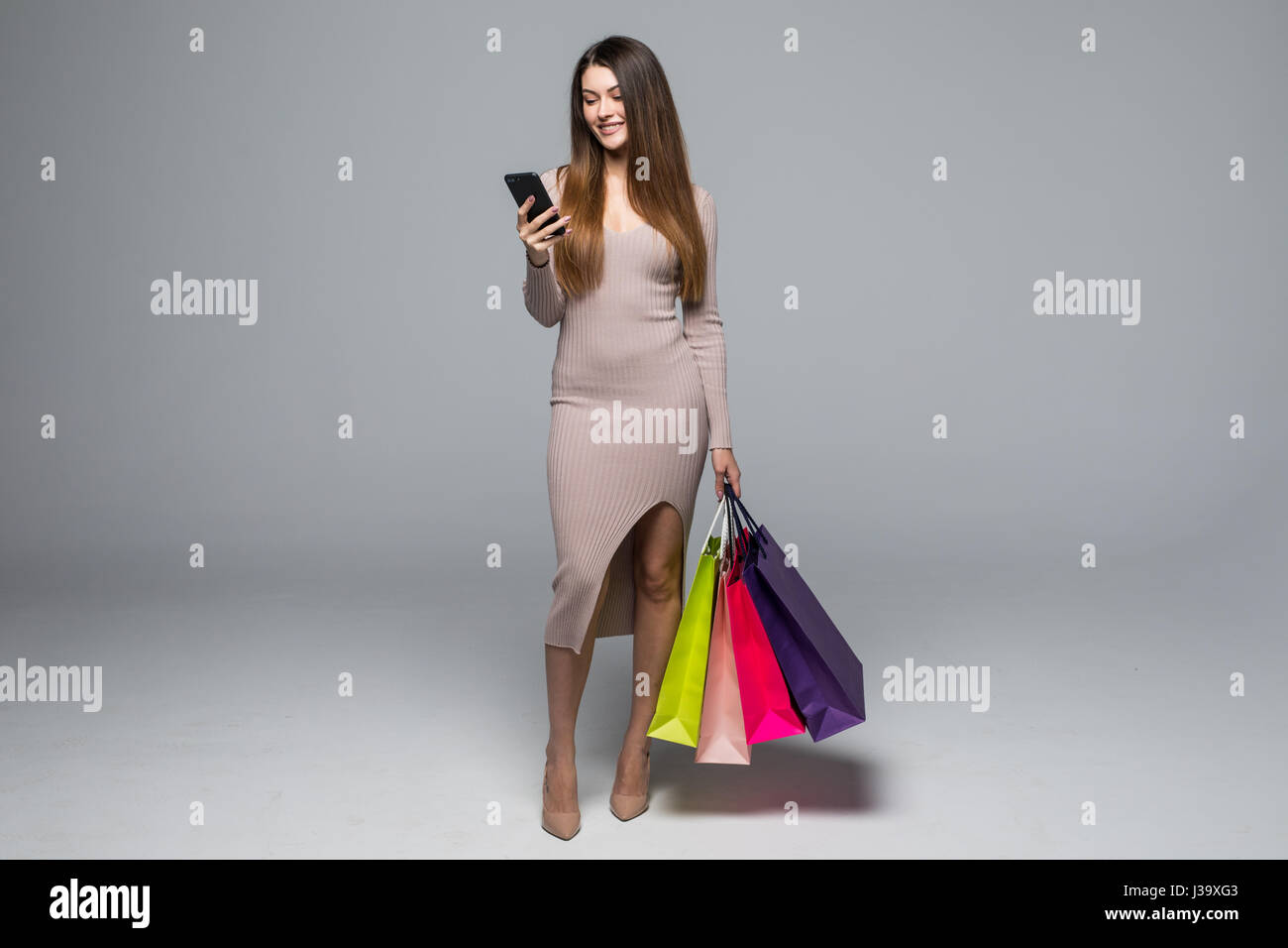 Young woman holding shopping bags and use mobile phone isolated on grey background - Stock Image