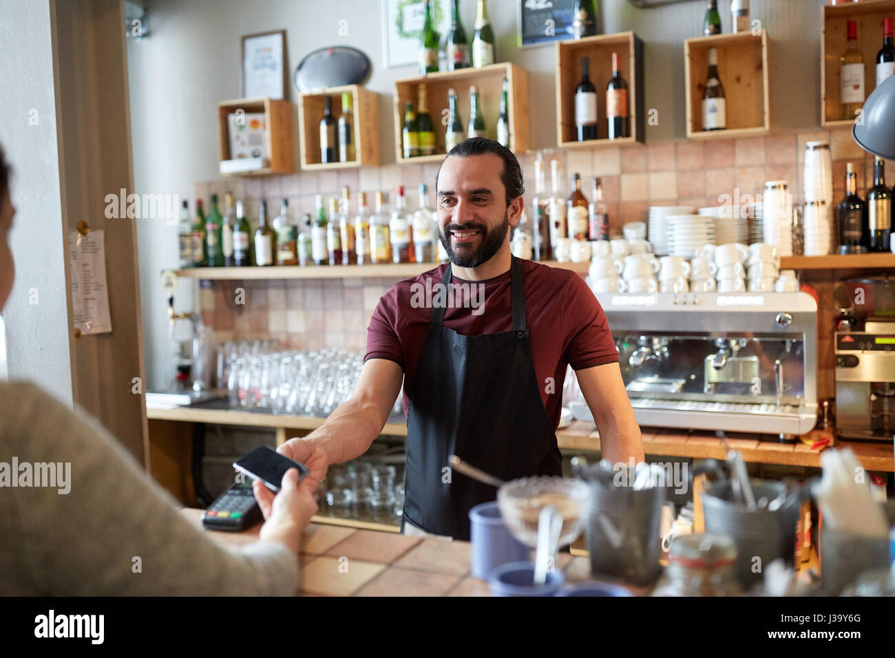 barman and woman with card reader and smartphone - Stock Image