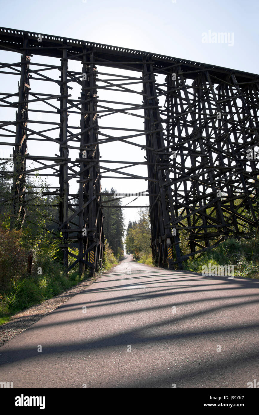 High strong old centenarian incumbent railway bridge constructed from stacked wooden beams intricately intertwined - Stock Image