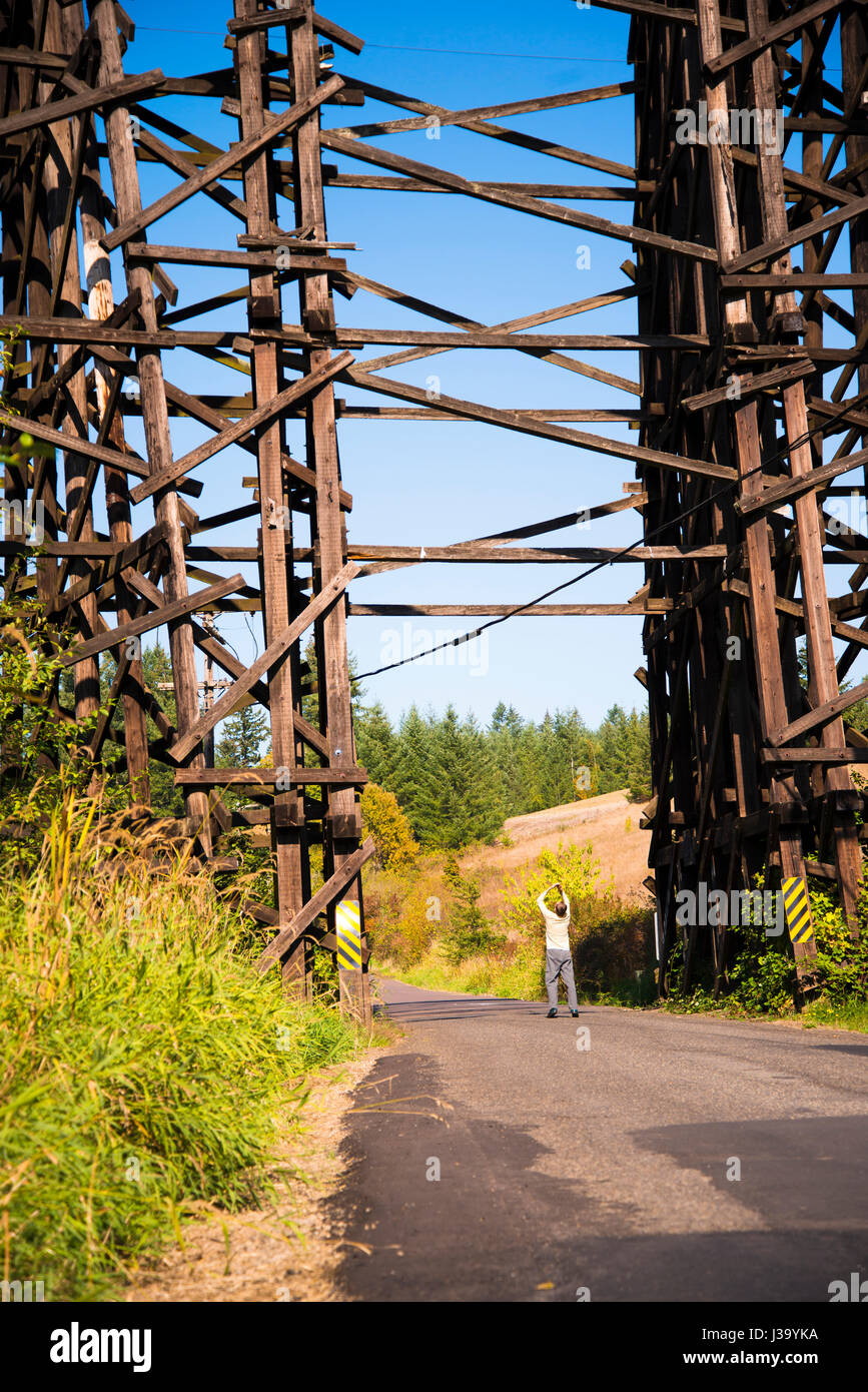 High current hundred years old railroad bridge across the valley through which the road passes constructed of wooden - Stock Image