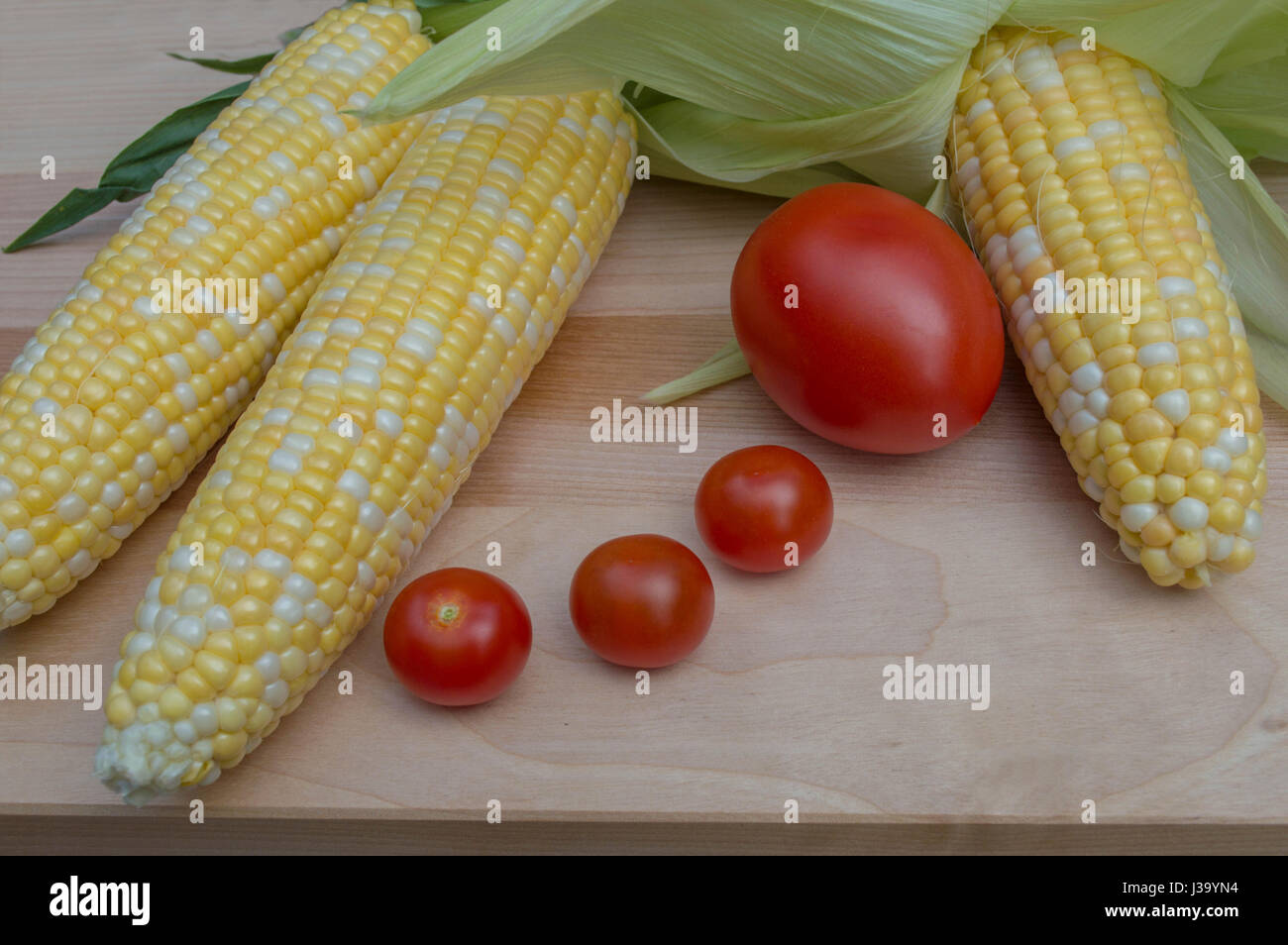 Four fresh tomatoes between three ears of corn on a maple cutting board. - Stock Image