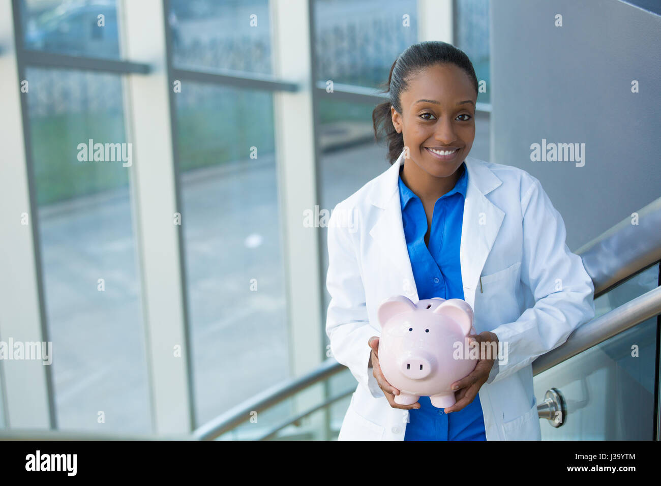 Closeup portrait, healthcare professional holding piggy bank isolated indoors clinic hospital background.  Health - Stock Image