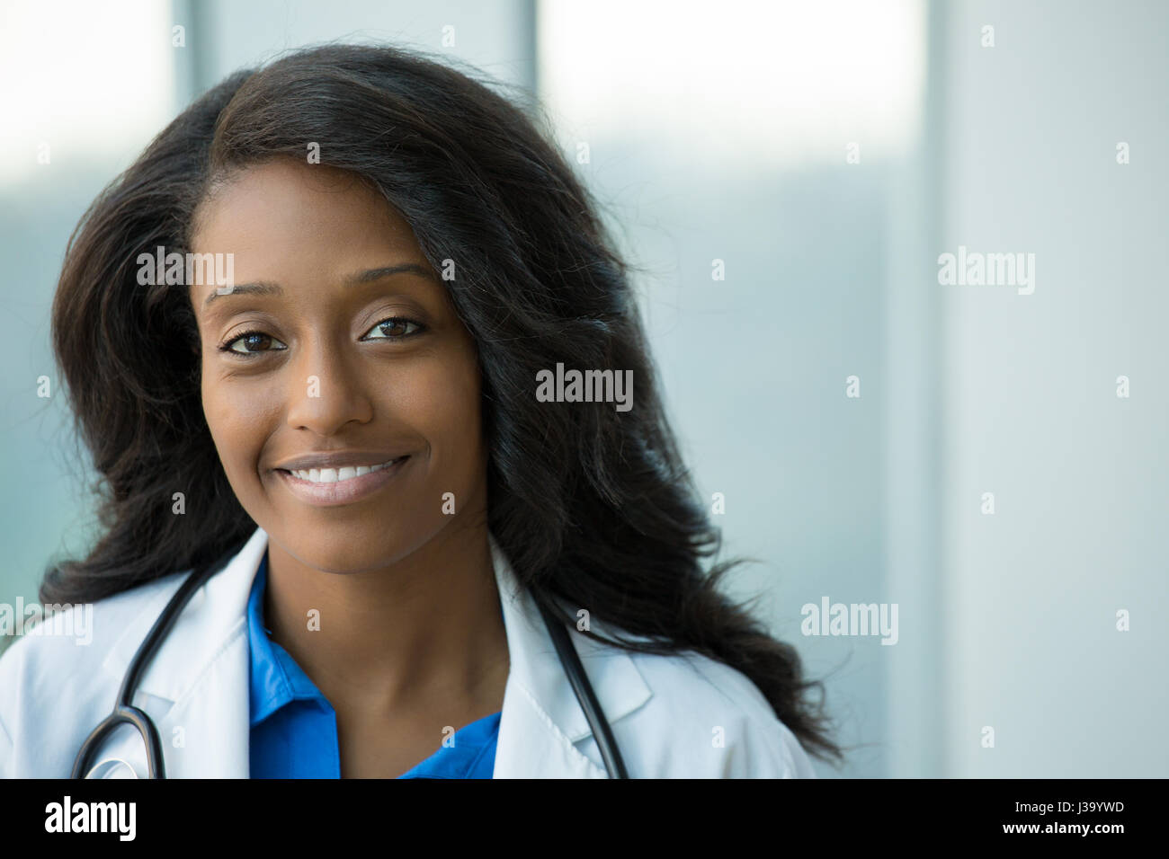 Closeup portrait of friendly, smiling confident female healthcare professional with lab coat, stethoscope, arms Stock Photo