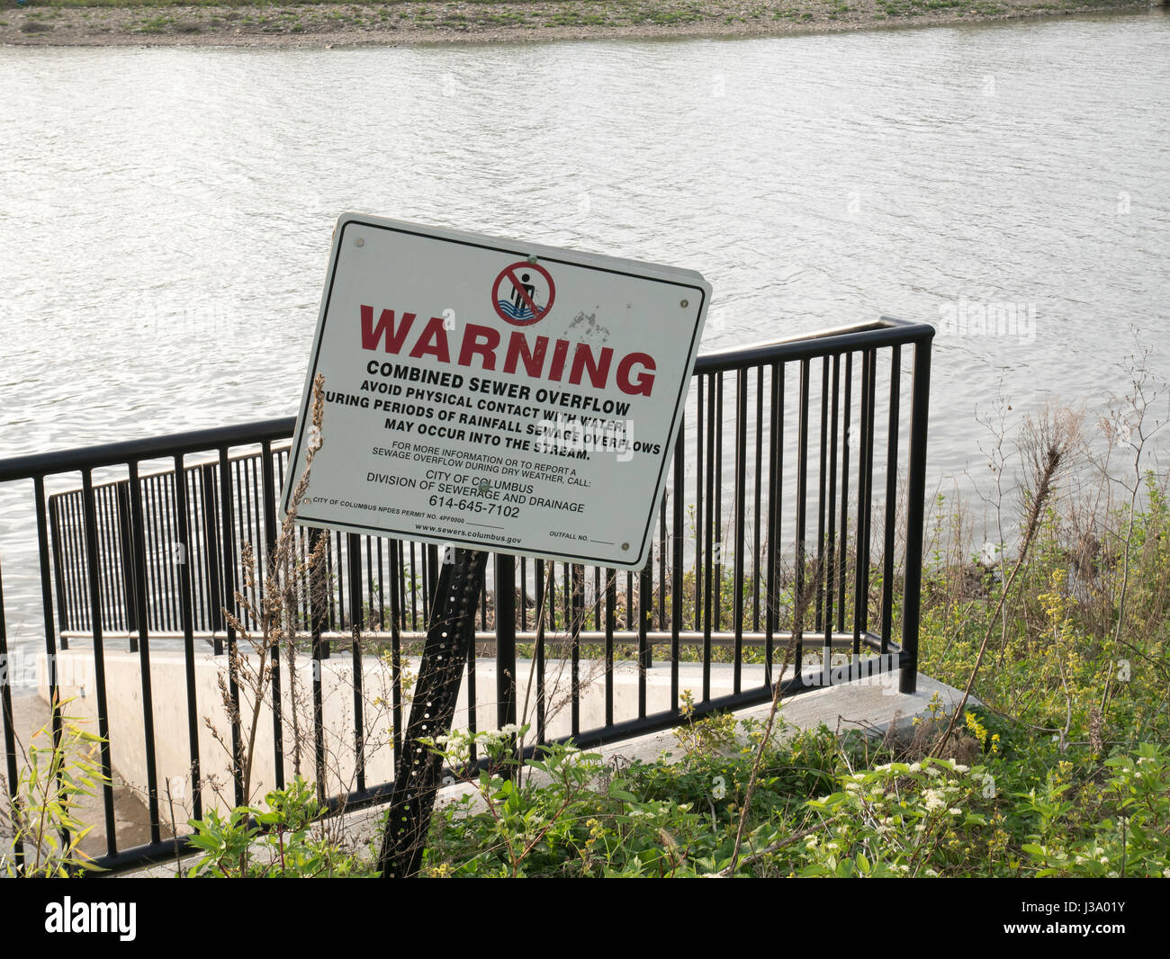 Water pollution warning on storm sewer overflow. Scioto River, Columbus, Ohio. - Stock Image