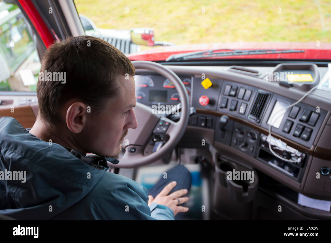 The truck driver sitting in the cab of modern comfort and ergonomic semi truck behind the wheel and interior dashboard - Stock Image