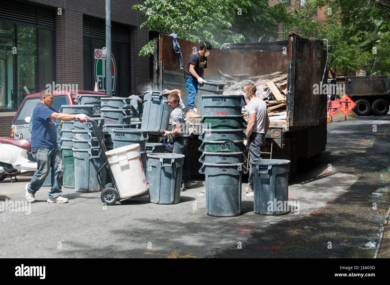 Four men removing debris from a construction site in large plastic bins n New York City - Stock Image