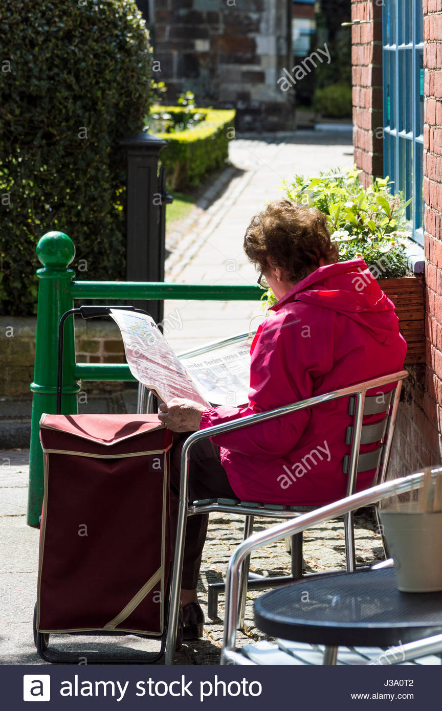 Older woman sat in the sunshine reading a newspaper Stock Photo