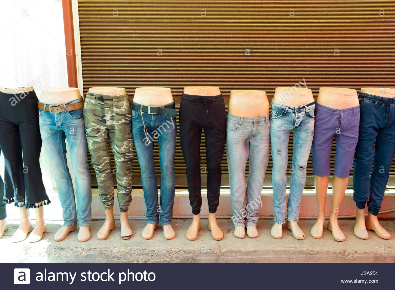Dummy legs displaying jeans on a traditional street market stall in the Turkish quarter of Nicosia, Cyprus Stock Photo