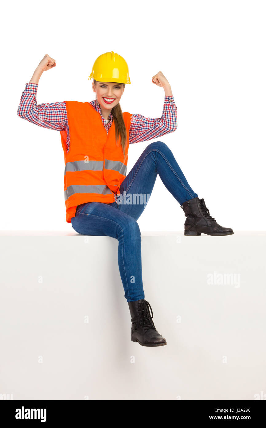 Smiling young woman in yellow hardhat, orange reflective vest, lumberjack shirt, jeans and black boots, sitting - Stock Image