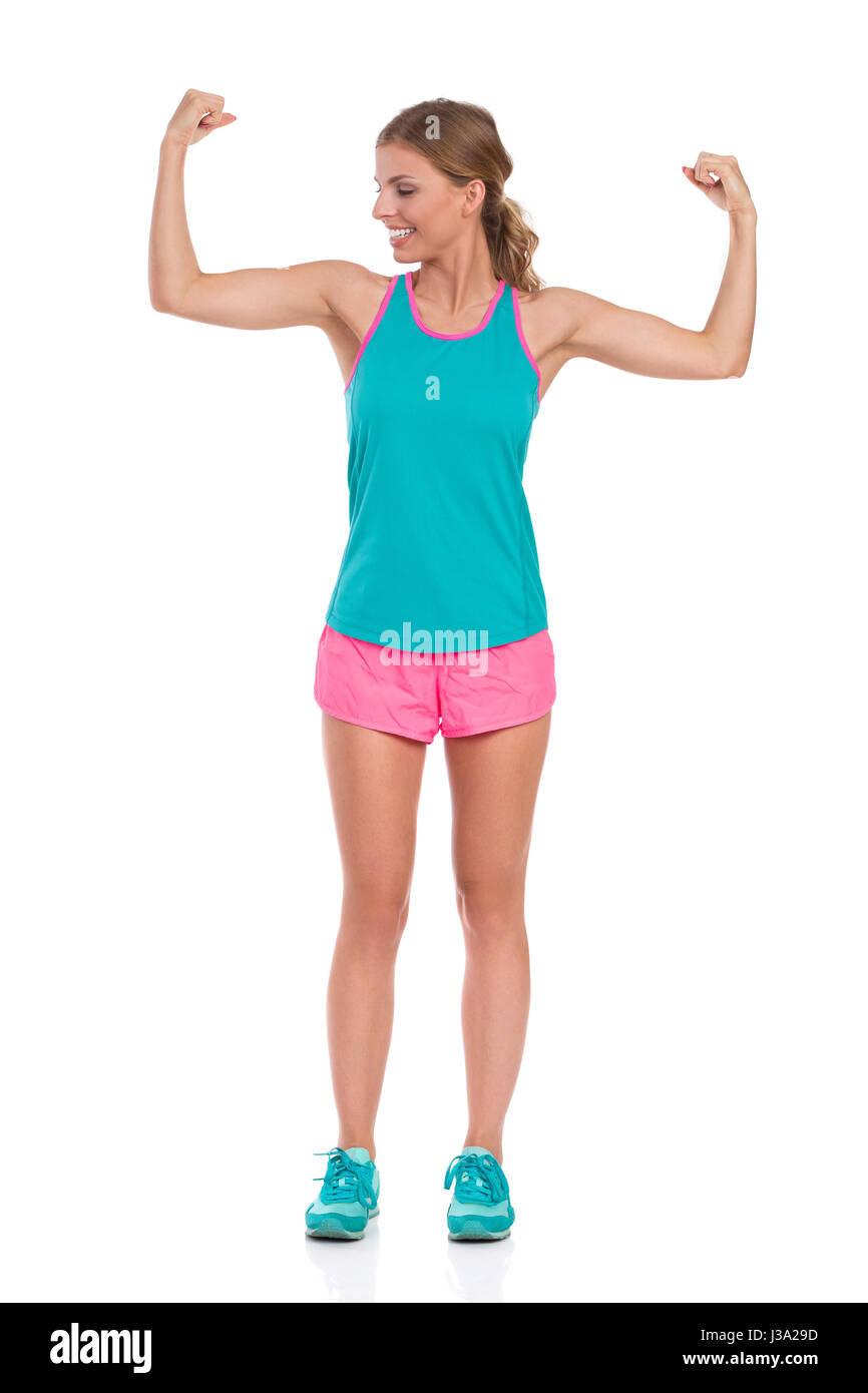 Smiling beautiful young woman in pink shorts, green tank top and sneakers standing with arms outstretched and flexing - Stock Image