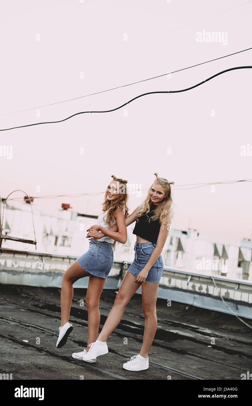 lifestyle and people concept: Fashion portrait of two stylish girls best friends wearing jeans skirts, outdoors. - Stock Image