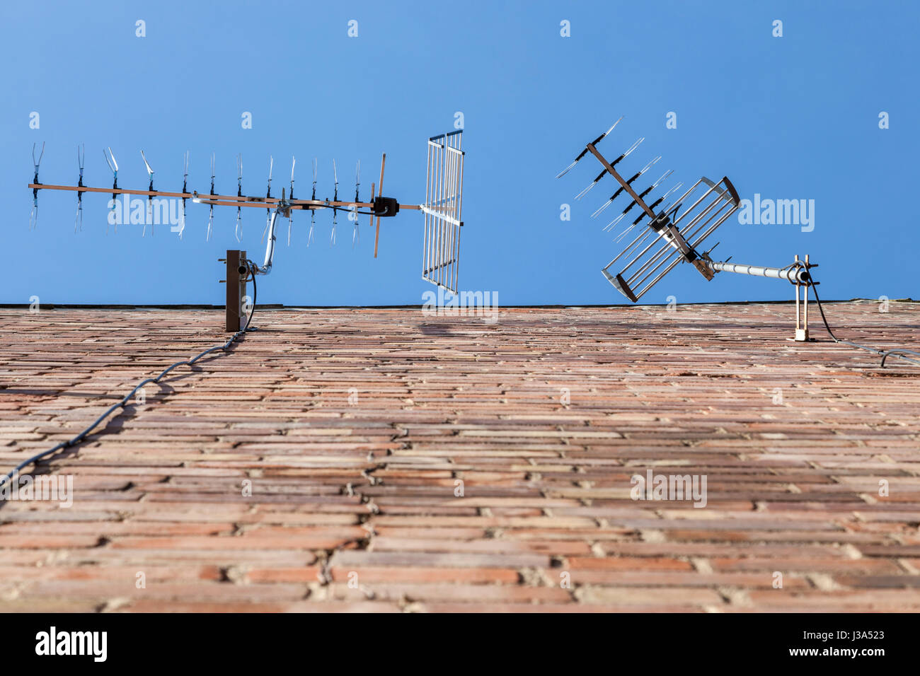 TV aerials on the side of a house, England, UK - Stock Image