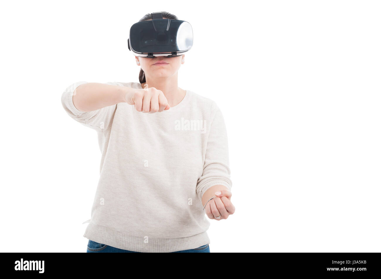 Woman with digital VR headset experiencing gaming simulation on white background with copyspace - Stock Image