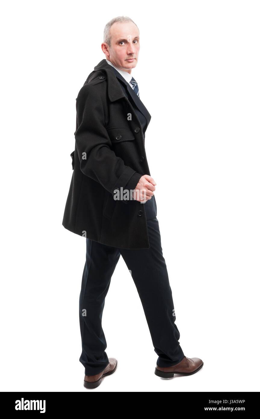 Full body of elegant man posing holding overcoat isolated on white background - Stock Image