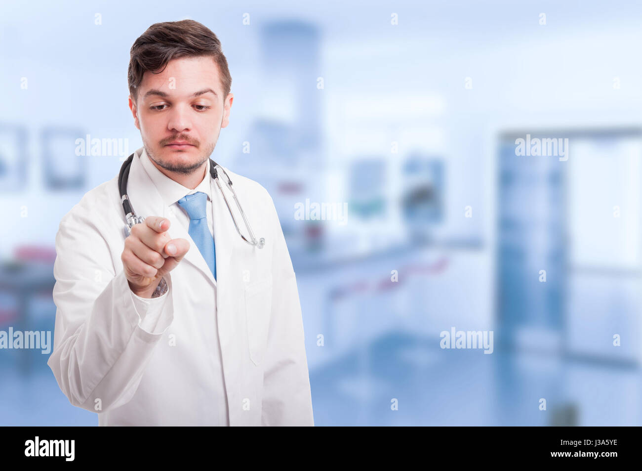 Male medic or doctor with stethoscope working with futuristic screen with copy space - Stock Image