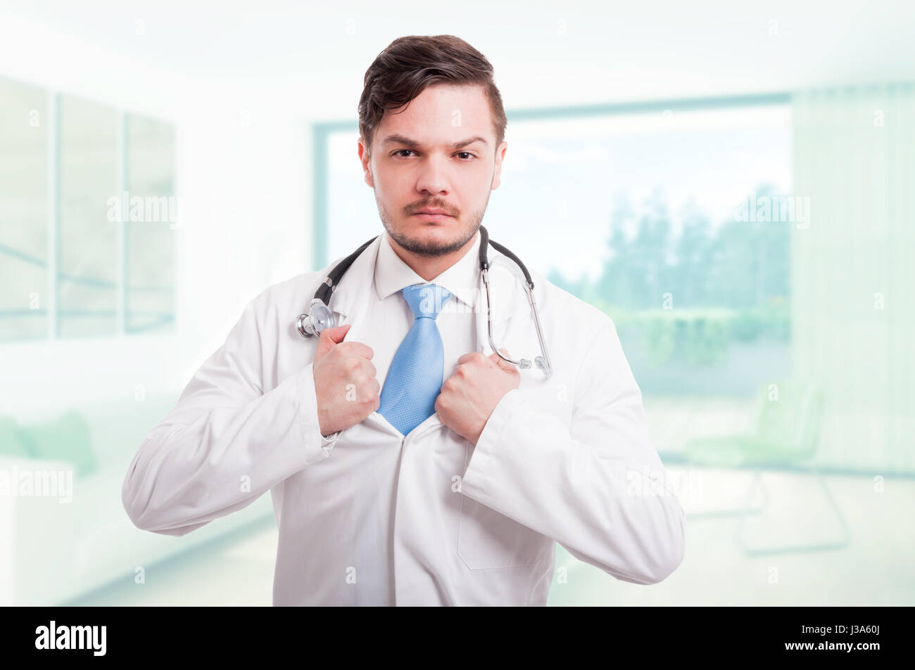 Handsome doctor tearing his lab coat acting brave as superhero concept - Stock Image