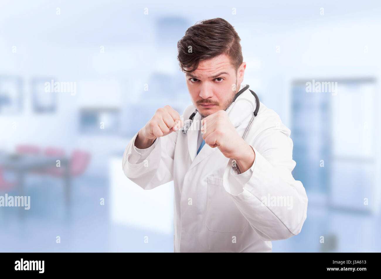 Doctor or medic acting violent and being ready to fight holding his fists up Stock Photo