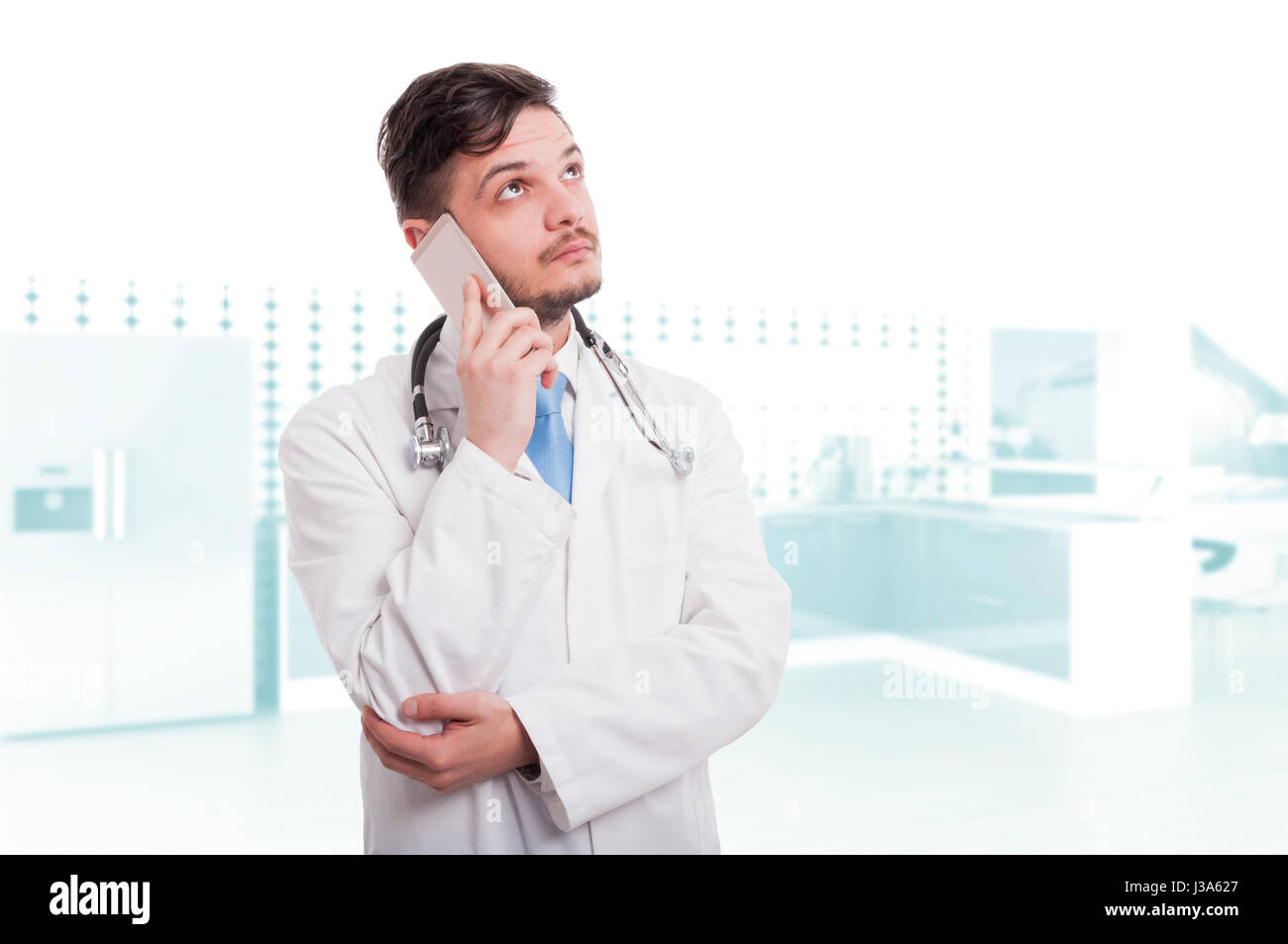 Professional doctor or medic talking on mobile phone in the hospital - Stock Image