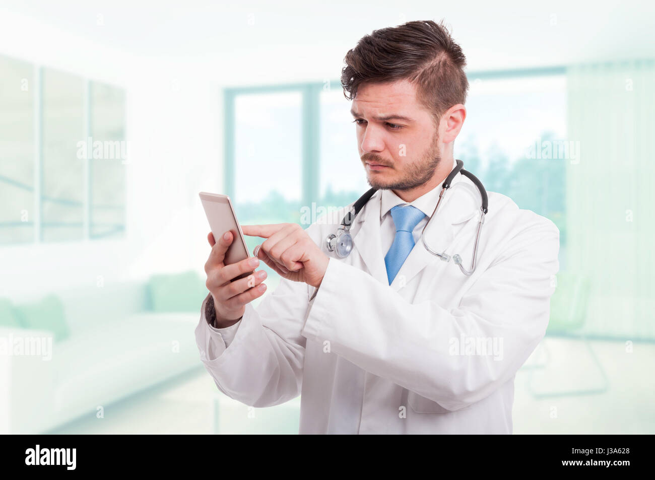 Modern doctor browsing or reading something on smartphone in his office - Stock Image