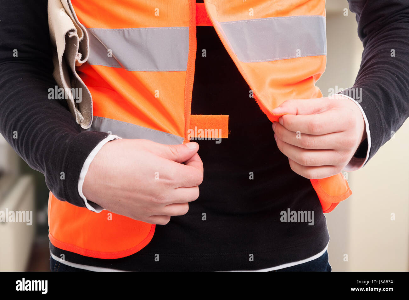 Closeup view of engineer with reflective vest getting ready for work - Stock Image