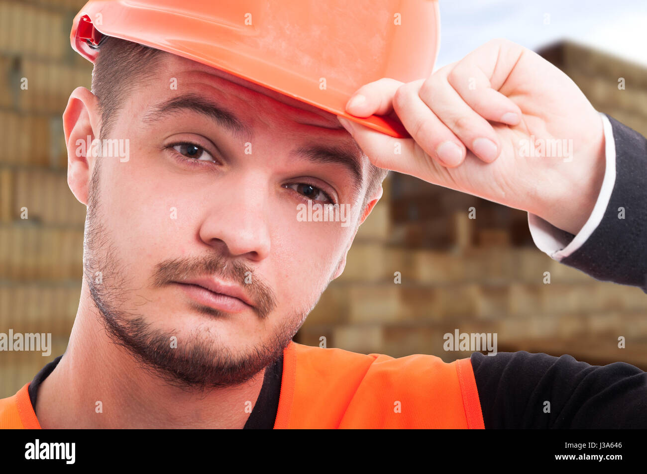 Close-up portrait of young engineer with protection helmet posing on construction site - Stock Image