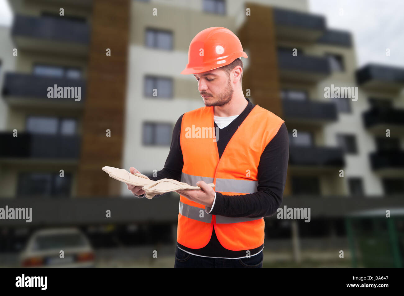 Male constructor outdoor at working place holding his protection gloves - Stock Image