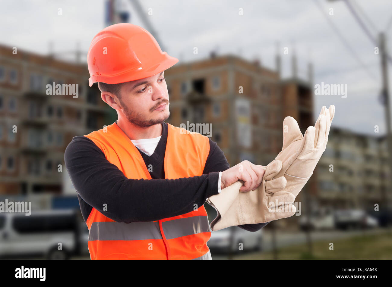 Builder putting protection gloves on hands and getting dressed for work - Stock Image