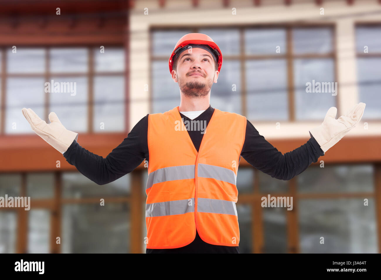 Self-confident construction worker rising his hands up as satisfaction concept - Stock Image