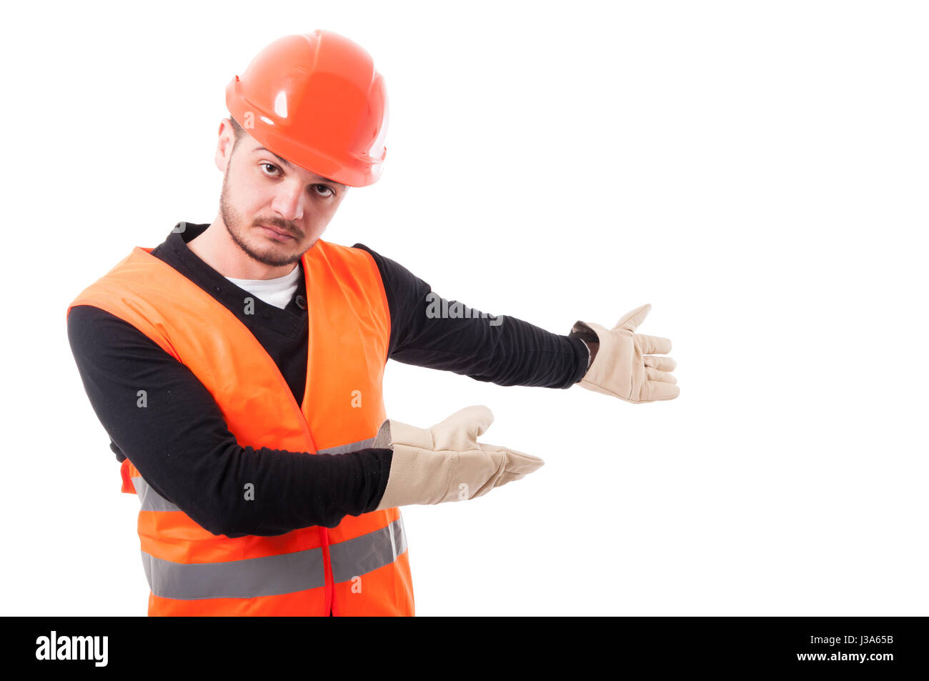 Architect or builder indicate something at blank copyspace behind him on white background - Stock Image