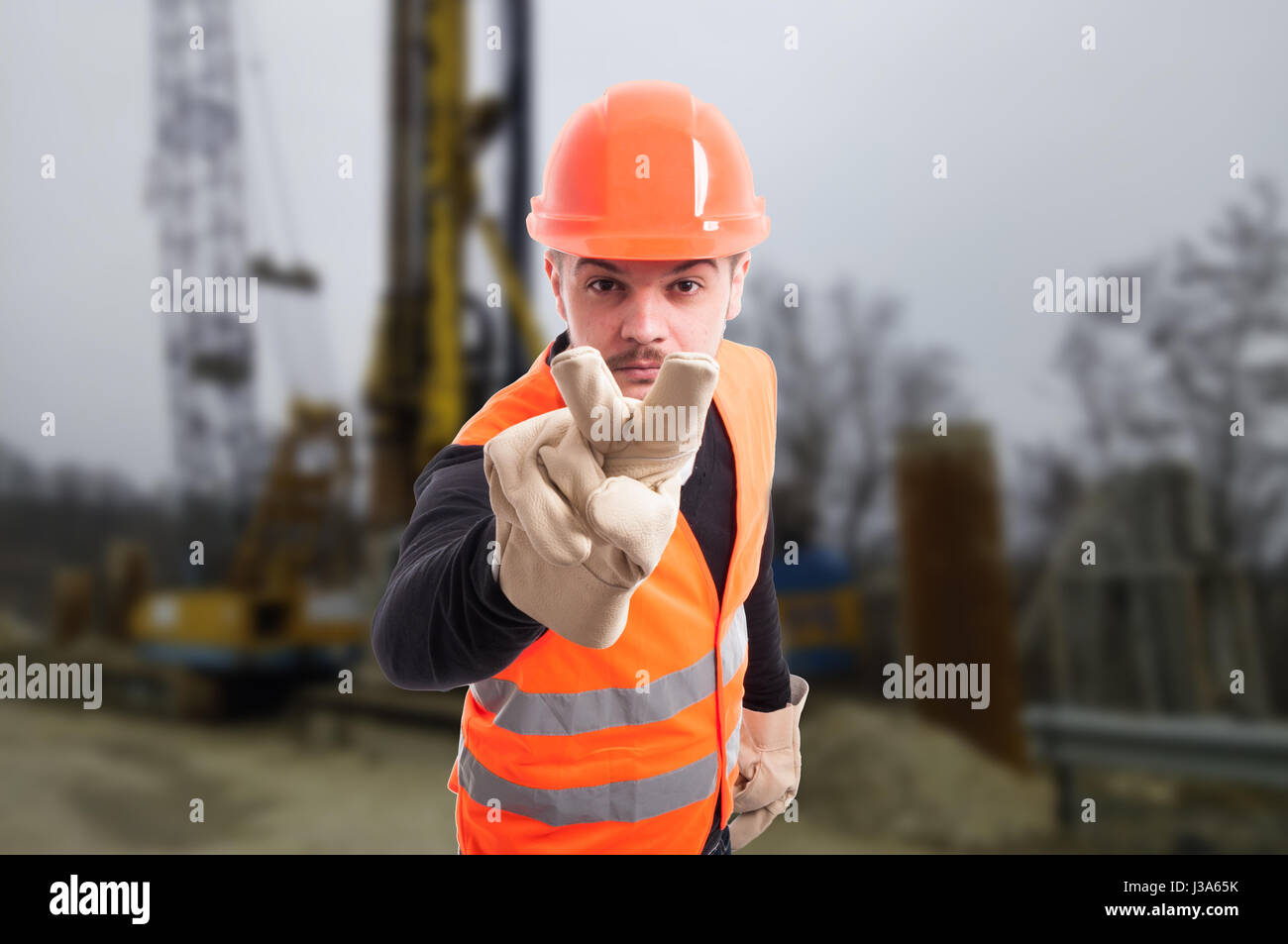 Attractive builder doing I'm watching you gesture as intimidation concept on construction site - Stock Image