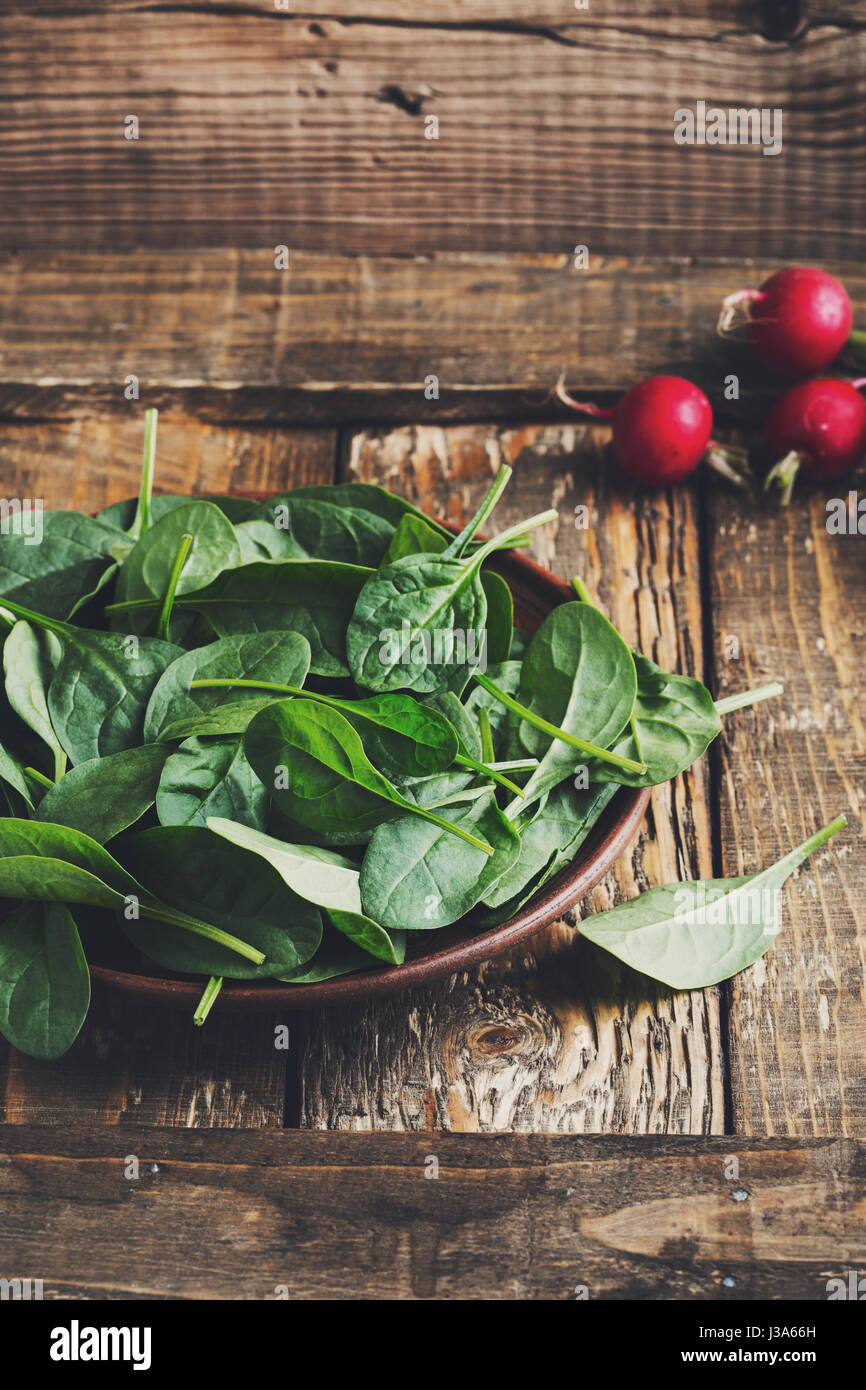 Fresh baby spinach leaves in rustic ceramic bowl Stock Photo