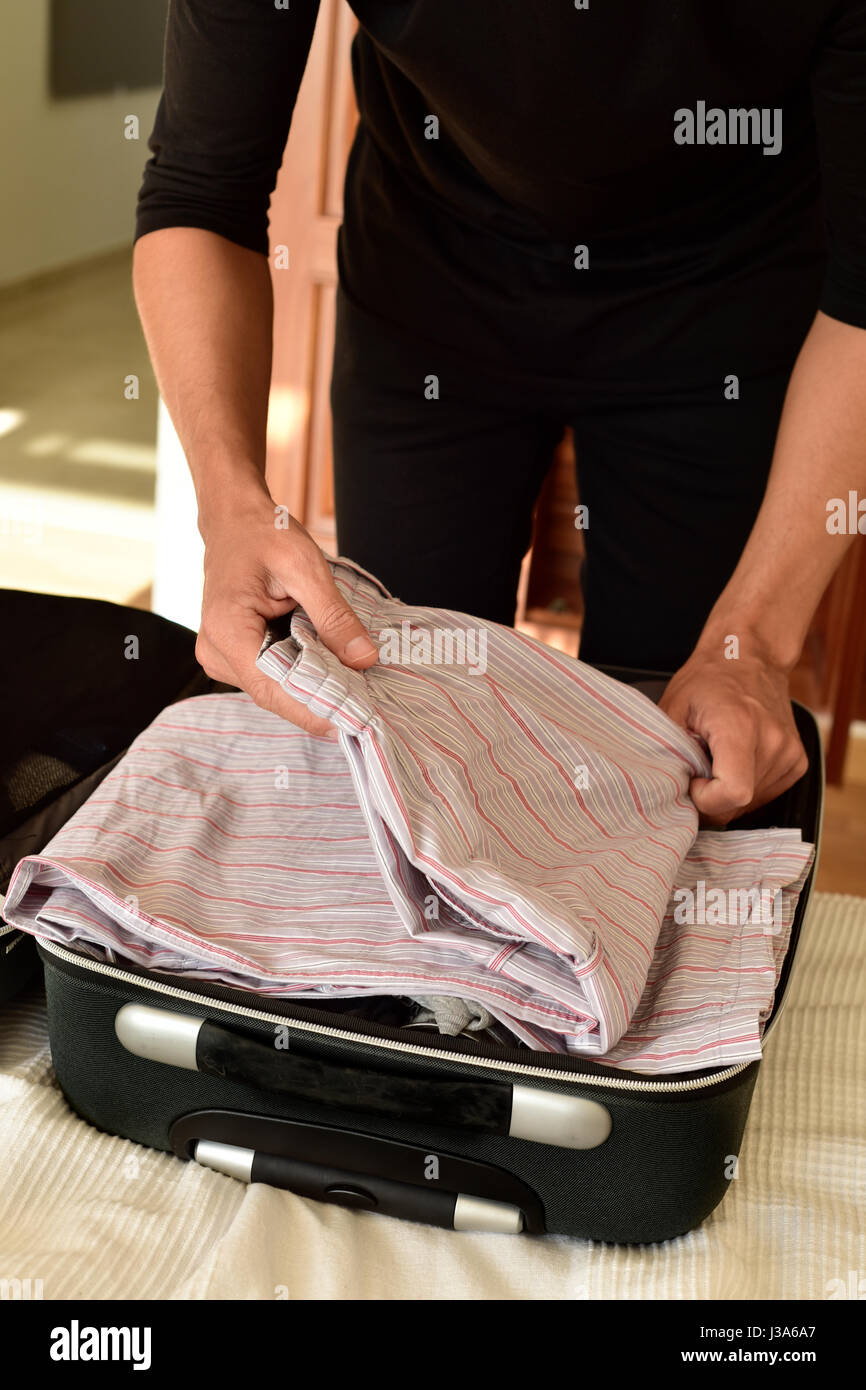 closeup of a young caucasian man putting clothes in his suitcase or putting them off, on the bed - Stock Image