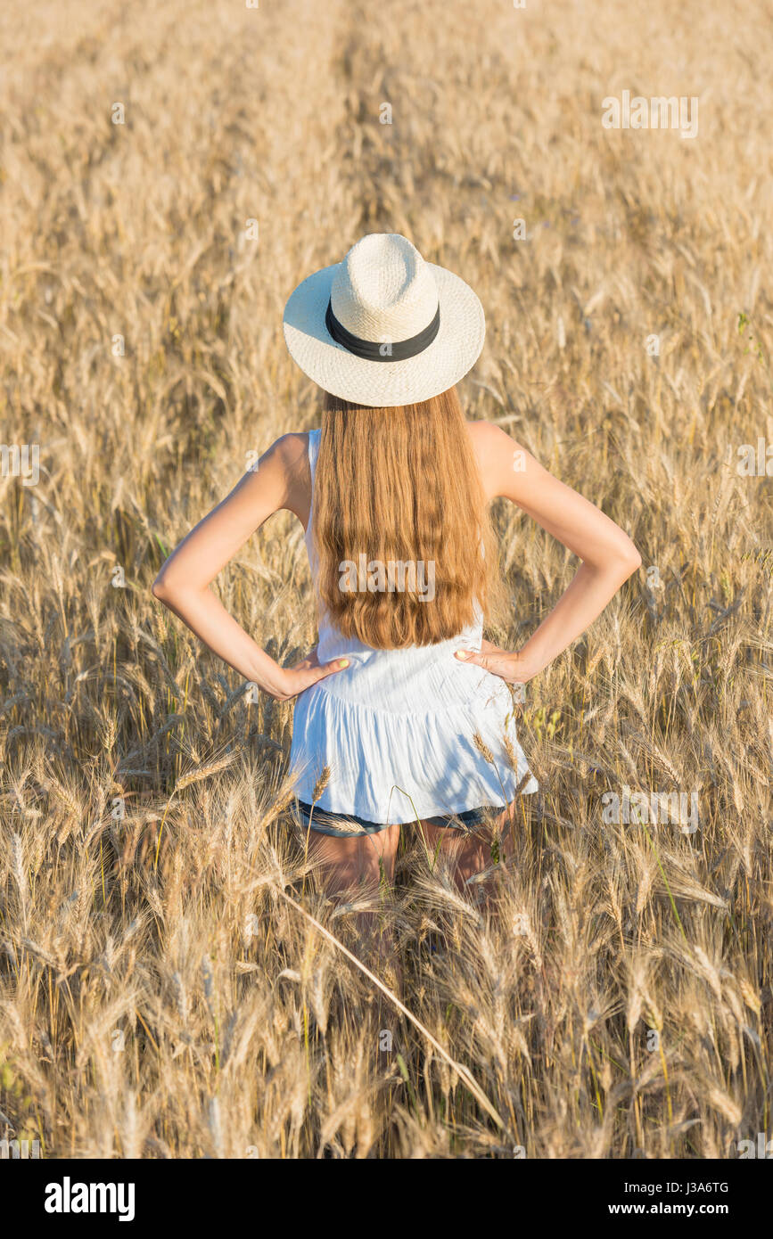 Beautiful young woman in straw hat and white shirt in golden wheat field Stock Photo