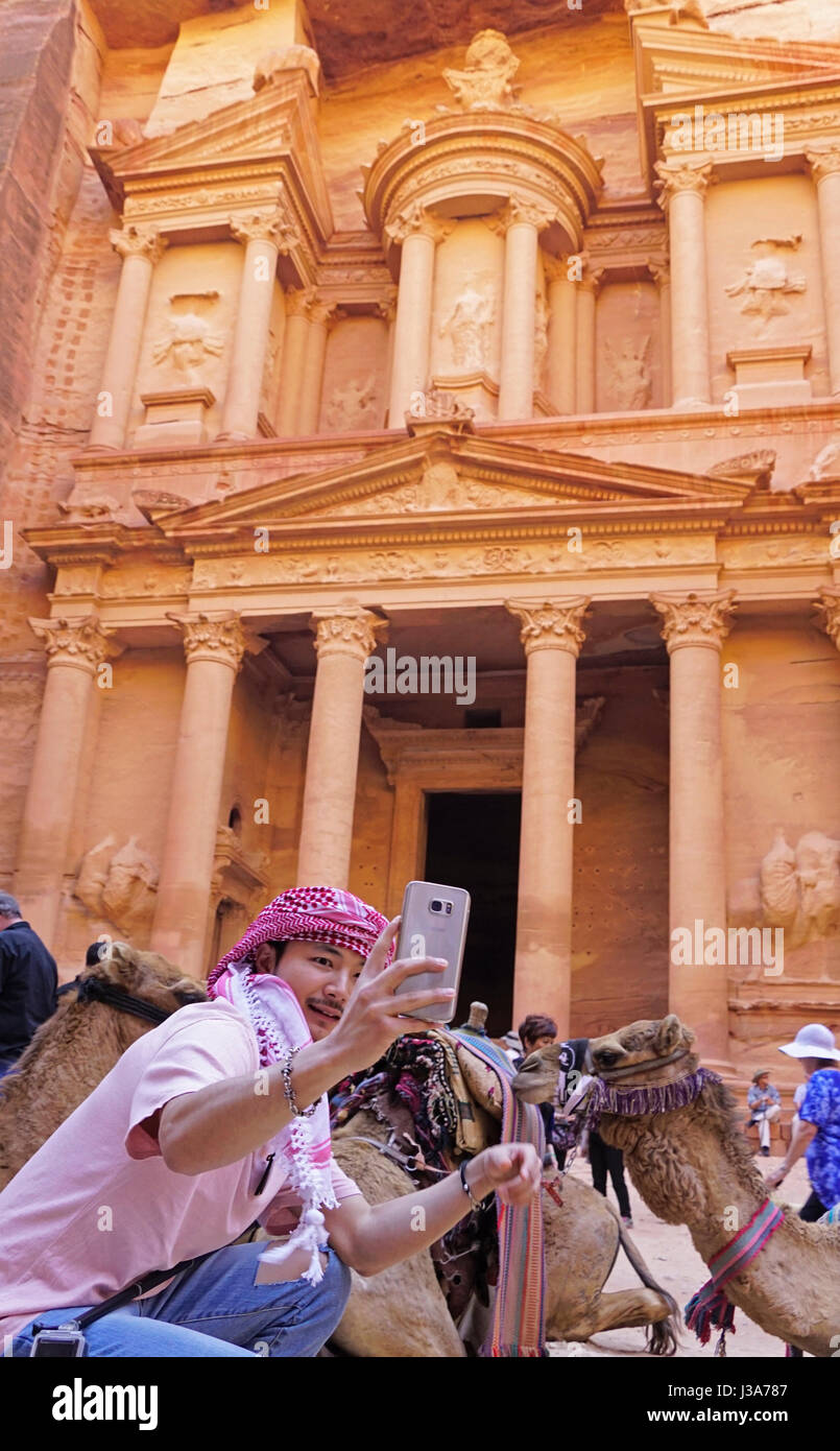 Tourist doing a selfie with camels at The Treasury in Petra. - Stock Image
