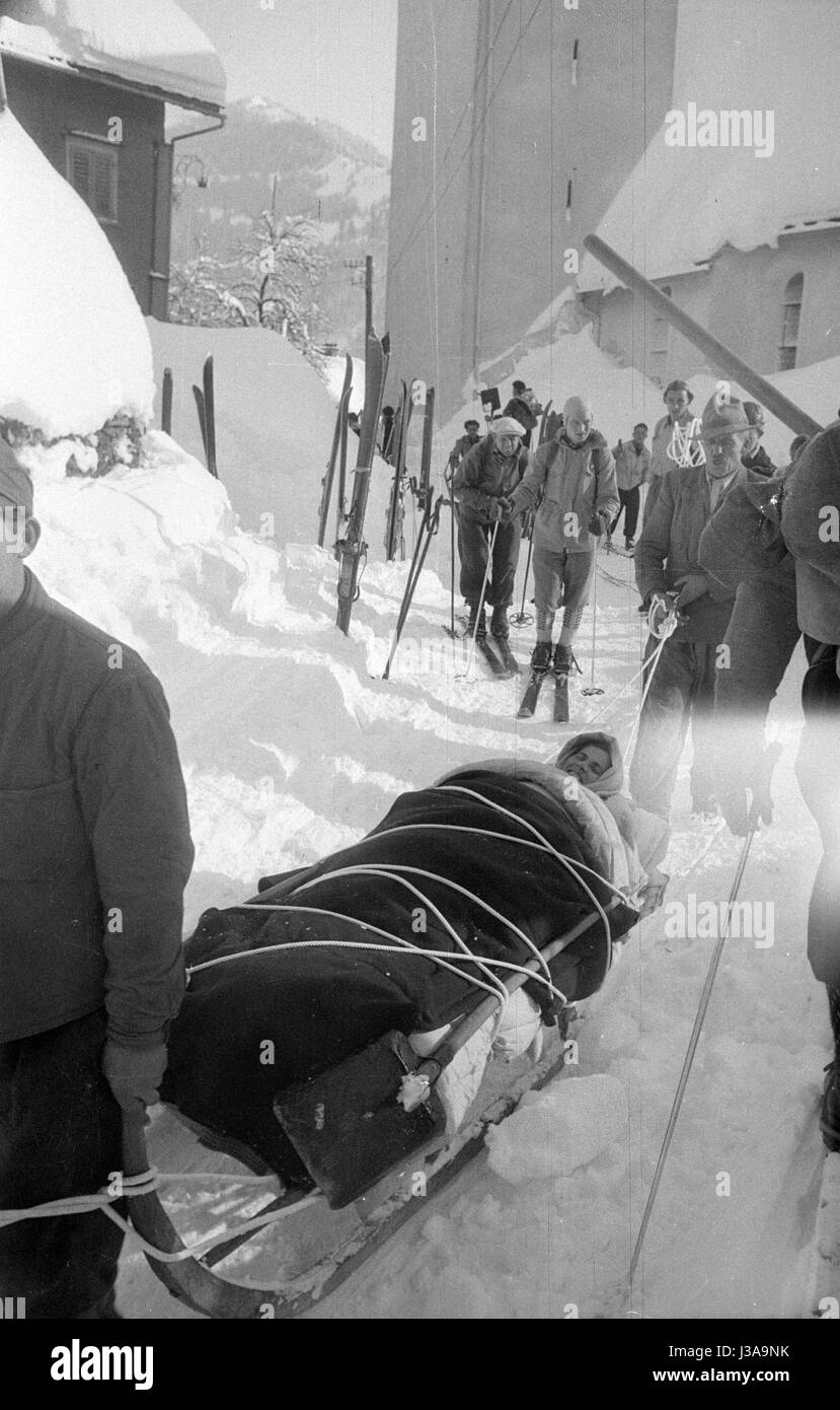 Rescued avalanche victim on a rescue sled after an avalanche in Blons, 1954 - Stock Image
