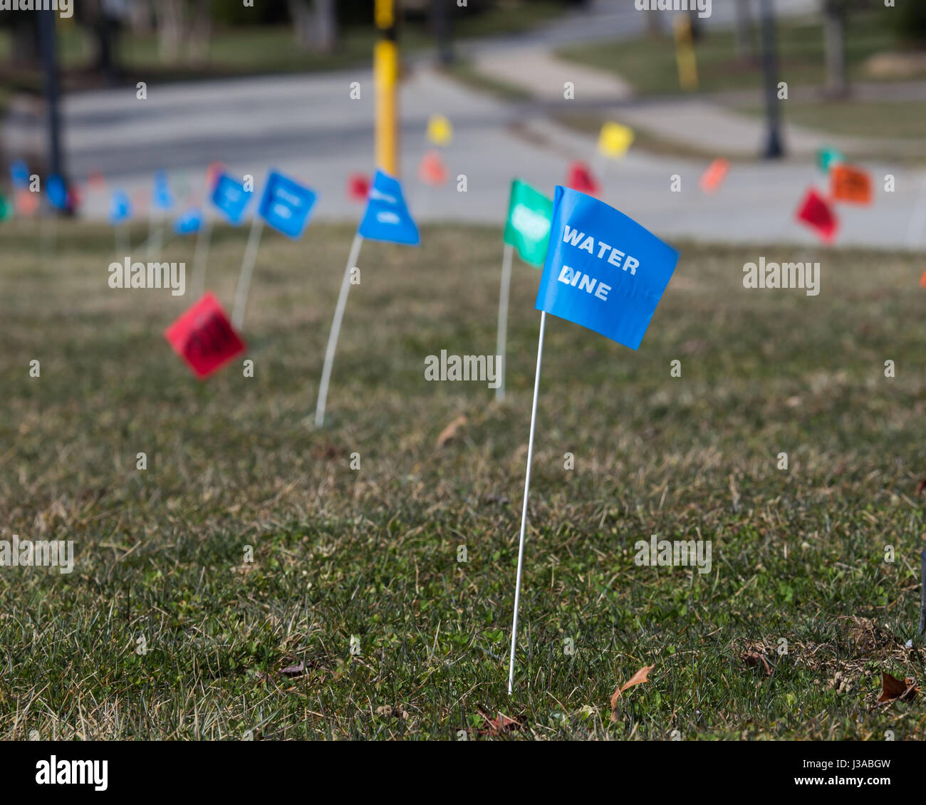 Utilities Location Flag Marking Underground Lines Such As Water, Electric, Telephone, Cable, Natural Gas and Sewer. - Stock Image