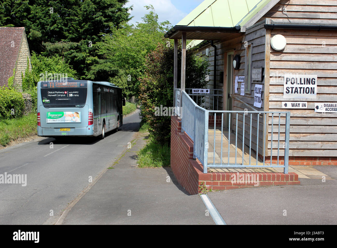 Local bus passes Garsington Village Hall polling station for the local council elections Oxfordshire - Stock Image