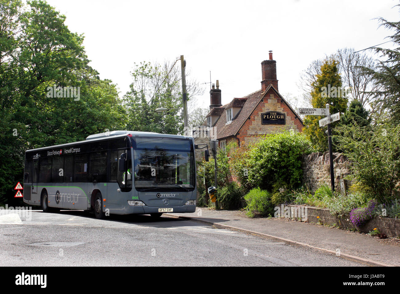 Local bus stopped outside The Plough Inn, Garsington Village, Oxford - Stock Image
