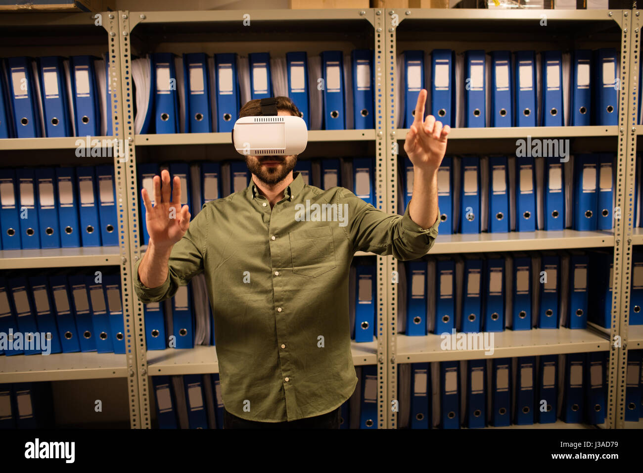 Businessman experiencing virtual reality in file storage room at workplace - Stock Image