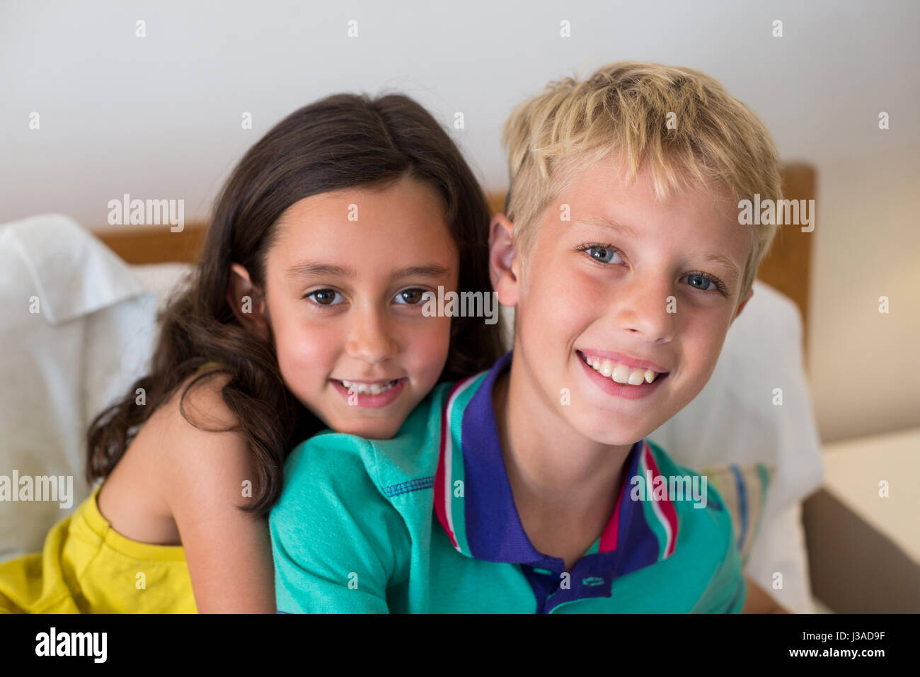 Portrait of smiling siblings embracing each other on bed in bedroom at home Stock Photo